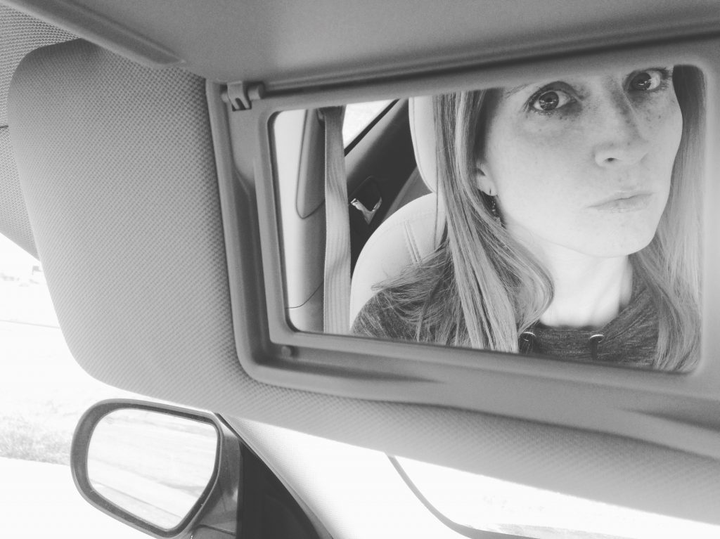 a photo of Kari looking in the rearview mirror and accepting feedback
