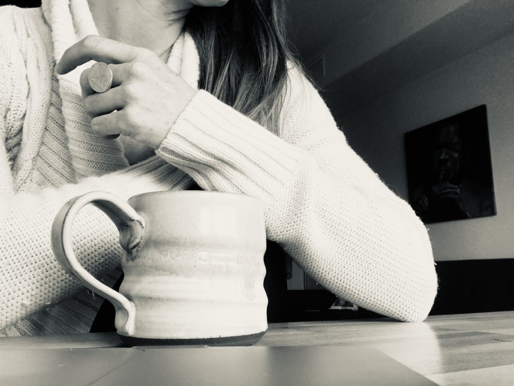 black and white image of a coffee mug and a yoga teacher's arm